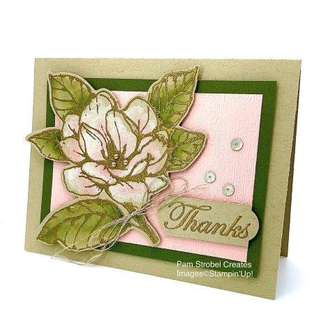 This gold embossed watercolored Magnolia Morning stamp set is on Crumb Cake card stock. It is watercolored with White Craft ink, allow to dry and add Blushing Bride ink to the base of each petal. the bold contrast of Mossy Meadow frames the image nicely as it flows over the edge of the border. Flower image cut using Magnolia Memory Dies. Enjoy more of this stamp set at my website : https://www.pamstrobelcreates.com/magnolia-morning-stamp-set